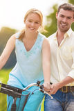 Happy Couple Having Fun Together Riding Bike Outdoors Stock Image