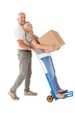 Happy couple having fun with trolley and moving box Royalty Free Stock Photos