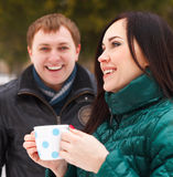 Happy couple having fun in the winter park drinking hot tea Royalty Free Stock Image