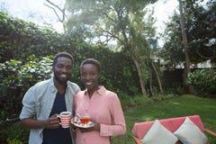 Couple having lemon tea and black coffee in garden. Happy couple having lemon tea and black coffee in garden Royalty Free Stock Photo