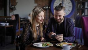 Happy couple having lunch together and looking at smartphone. Man and woman using digital gadget laughing at pictures. Happy couple are having lunch together and stock video