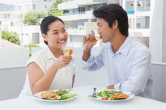 Happy couple having a meal together with white wine Stock Image