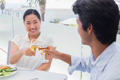 Happy couple having a meal together with white wine Stock Photography