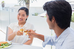 Happy couple having a meal together with white wine Stock Photos