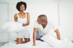 Happy couple having a pillow fight Stock Photo
