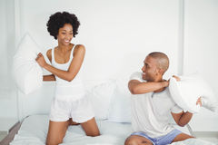Happy couple having a pillow fight Royalty Free Stock Image