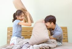 Couple having pillow fight on bed Stock Photo