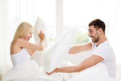 Happy couple having pillow fight in bed at home. People, family, bedtime and fun concept - happy couple having pillow fight in bed at home stock image
