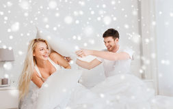 Happy couple having pillow fight in bed at home Royalty Free Stock Images