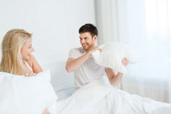 Happy couple having pillow fight in bed at home Stock Images