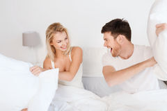 Happy couple having pillow fight in bed at home. People, family, fun, bedtime and fun concept - happy couple having pillow fight in bed at home royalty free stock photography
