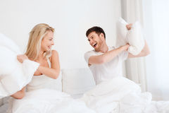 Happy couple having pillow fight in bed at home Royalty Free Stock Image