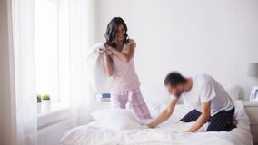 Happy couple having pillow fight in bed at home. People, family, fun, bedtime and fun concept - happy couple having pillow fight in bed at home stock video footage