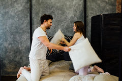 Happy couple having pillow fight in bed at home stock photos