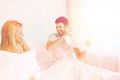 Happy couple having pillow fight in bed at home Royalty Free Stock Photography
