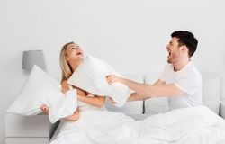 Happy couple having pillow fight in bed at home. People and fun concept - happy couple having pillow fight in bed at home royalty free stock photos