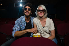 Couple having popcorn while watching movie in theatre stock photo