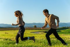 Happy couple having a race outdoors. Stock Image