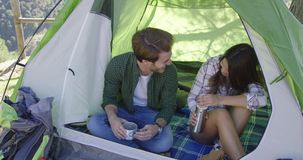 Happy couple having rest. Young happy tourists sitting in tent and drinking tea while having rest in mountains stock footage
