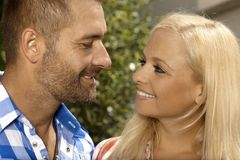Happy couple having a romantic moment outdoors. Attractive blonde, smiling women and stubbly handsome man Stock Images