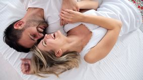 Happy couple having romantic times in bedroom. Happy young couple having romantic times in bedroom Royalty Free Stock Images