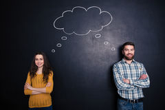 Happy couple having the same thoughts over black board background. Happy couple standing with arms crossed and having the same thoughts over black board stock photo