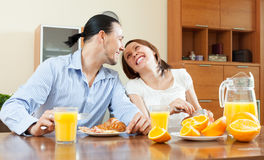 Happy couple having scrambled eggs with bacon in morning Stock Images