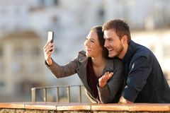 Happy couple having a video call or taking selfies. With a smart phone in a balcony at sunset royalty free stock photos
