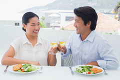 Happy couple having white wine with a meal Stock Photo