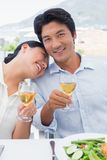 Happy couple having white wine with a meal Stock Photography