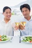 Happy couple having white wine with a meal Royalty Free Stock Photos