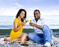 Happy couple having wine on beach. Young romantic couple celebrating with wine at the beach stock photo