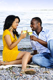 Happy couple having wine on beach. Young romantic couple celebrating with wine at the beach looking at each other stock photography