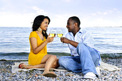 Happy couple having wine on beach. Young romantic couple celebrating with wine at the beach looking at each other royalty free stock photography