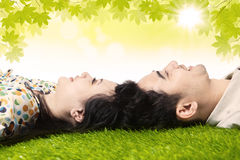Happy couple with heads together under leaves Royalty Free Stock Photo