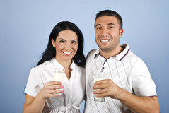 Happy couple healthy with milk glasses. Happy couple healthy holding glasses with milk and standing together in a hug showing smiles for you on blue background Stock Photo