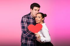 Happy couple with a heart in hand on pink background Stock Photography