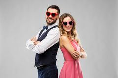Happy couple in heart-shaped sunglasses royalty free stock photography