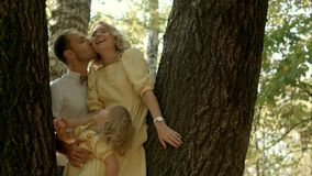 Happy couple with her little daughter kissing over a forest background stock photography