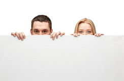 Happy couple hiding behind big white blank board. People, advertisement and information concept - happy couple hiding behind big white blank board Royalty Free Stock Images