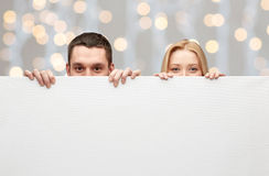 Happy couple hiding behind big white blank board. People, advertisement and information concept - happy couple hiding behind big white blank board over holidays Royalty Free Stock Image