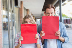 A happy couple hiding themselves behind red bags Royalty Free Stock Images