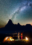 Happy couple hikers raised their hands up under the stars and Milky way near bonfire and tent Stock Photo