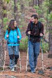 Happy couple hikers talking together hiking. Happy couple hikers talking together on outdoor nature walk. Young multiracial people hiking outdoors in forest stock image