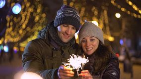 Cute young couple holding sparklers stock footage