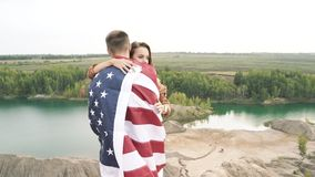 Happy couple holding the American flag in nature. Independence Day, lifestyle, travel concept.  stock video