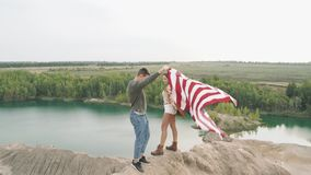 Happy couple holding the American flag in nature. Independence Day, lifestyle, travel concept.  stock video footage