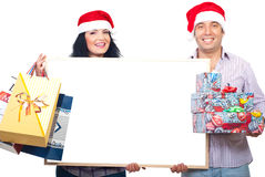 Happy couple holding banner and Xmas gifts stock photo