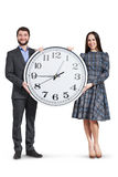 Happy couple holding big clock Royalty Free Stock Photo