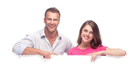 Happy couple holding a blank billboard. Portrait of a happy couple holding a blank billboard on white background royalty free stock photos